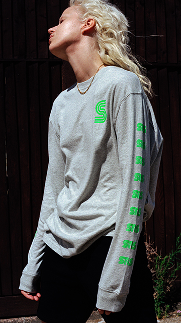 Girl wearing a long sleeves SNS t-shirt in grey and green and looking at the sun.
