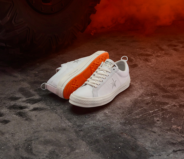 A pair of Converse One Star x Carhartt WIP sneakers in white and orange.
