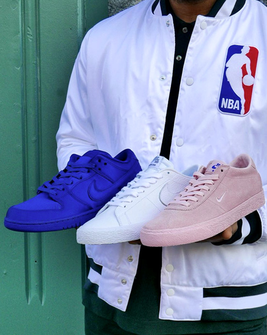 A man holding three Nike SB x NBA sneakers in blue, white and pink.