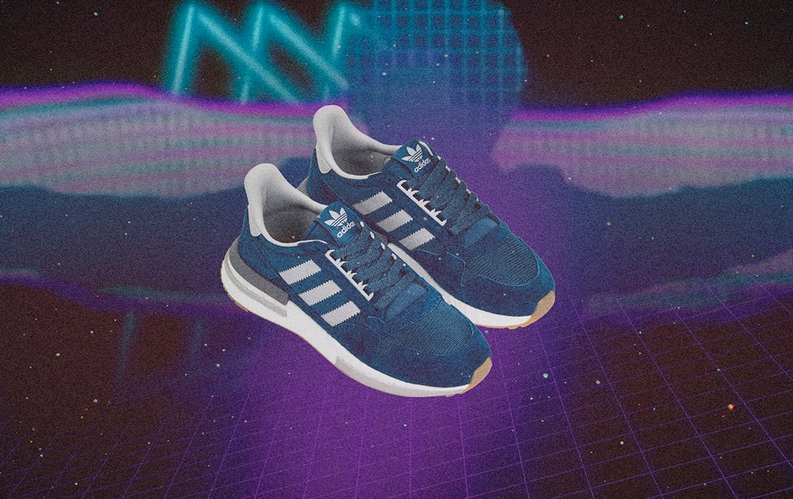 A pair of adidas ZX500 sneakers in blue over a purple retro-futuristic background.