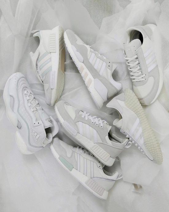 "Various adidas ""Never Made"" sneakers in white and light tones of green and pink laying over a white fabric."