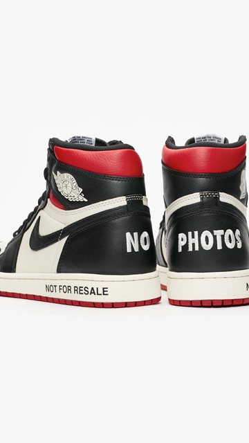 "A pair of Air Jordan 1 ""Not For Resale"" sneakers in red and black over a white background."