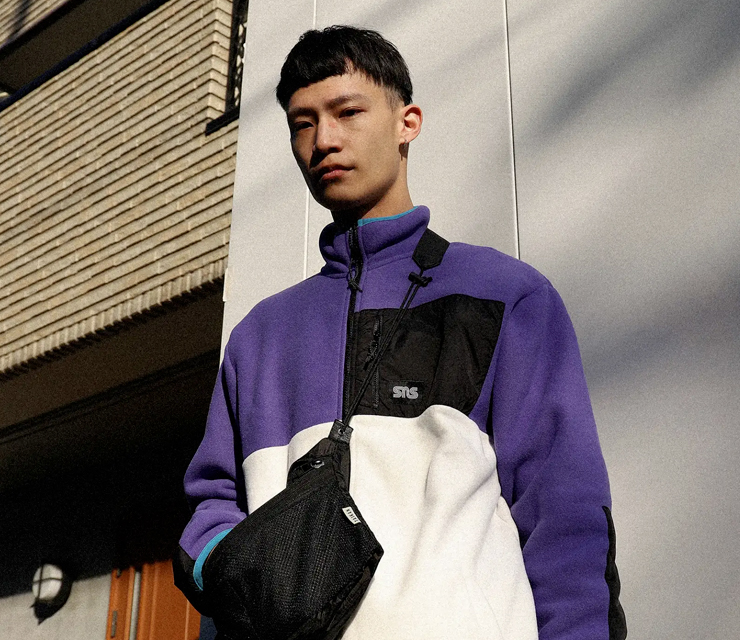 A man wearing a Sneakersnstuff purple fleece jacket and a black Taikan bag, standing in front of a grey wall in a street in Tokyo