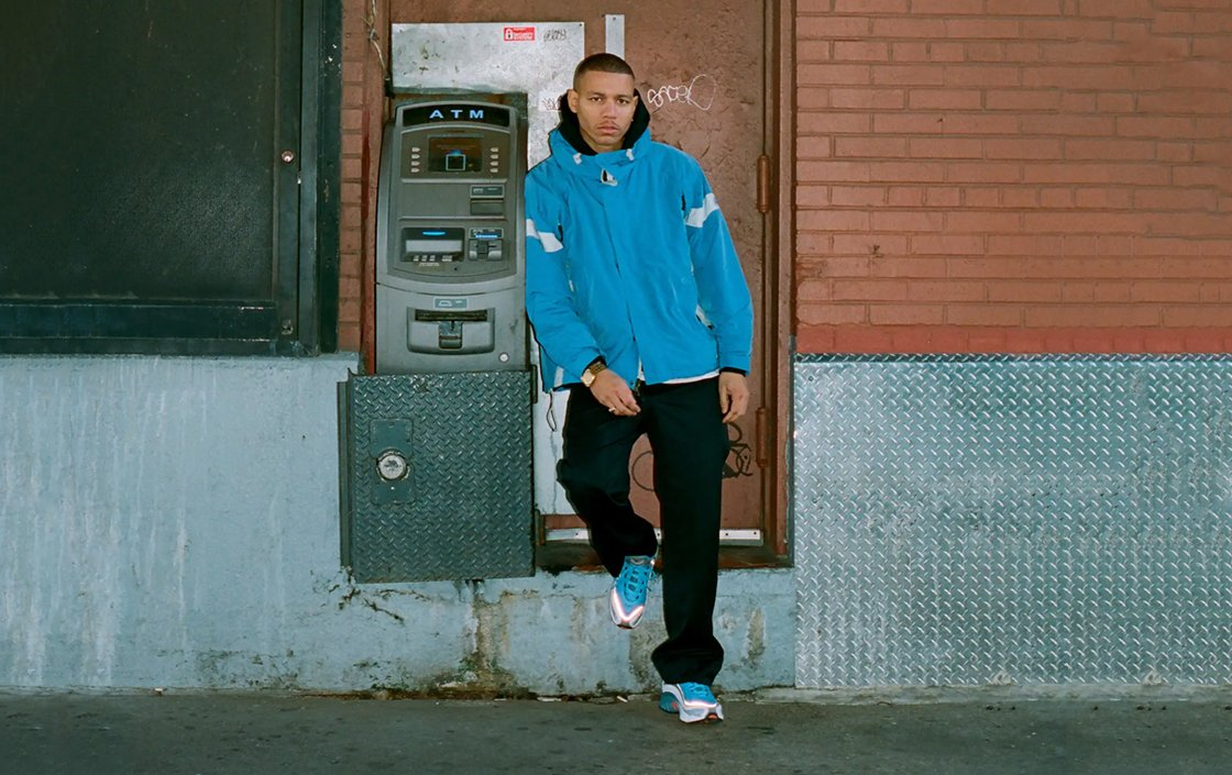 A man wearing Reebok Daytona DMX sneakers in blue and standing beside an ATM in front of a orange brick wall.