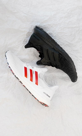 Two adidas Ultraboost sneakers in black and white laying over a white background.