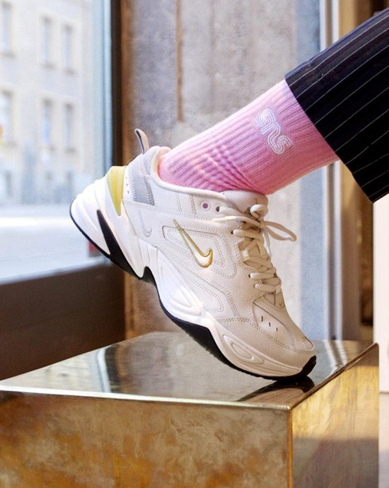 A person wearing a Nike M2K Tekno sneaker in white and yellow with a pink sock from SNS.