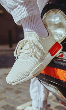 A person wearing a pair of adidas NMD R1 sneakers in white and stepping on the bumper of a car.
