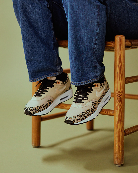 A girls wearing a pair of Nike Air Max 1 Animal Print sneakers in beige and leopard skin pattern. she is sitting on a wood chair that stands over an olive green background.