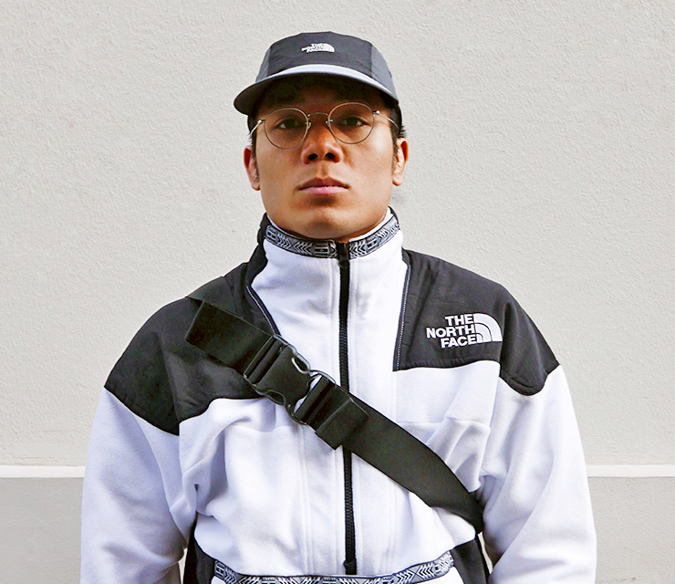 A man wearing a black hat and a black and white fleece anorak from the North Face Rage 92 collection. he is looking at the camera and standing in front of a white wall.