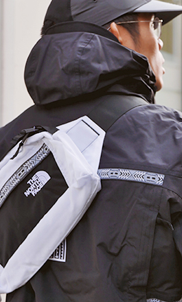 A young man wearing a hat, a windbreaker and a chest bag from the The North Face Rage 92 collection in white and black.