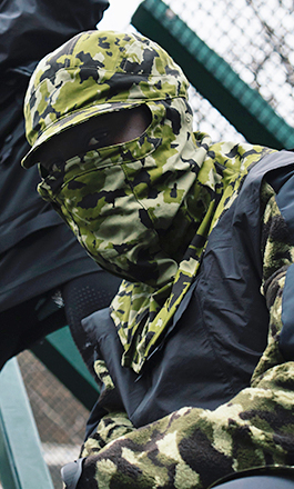 Man wearing a balaclava in camouflage pattern from the Nike x Mathew M. Williams collection. He is crouching in the steps of a stair in an outdoor area. There is another person behind him also dressed in clothes of the same collection.