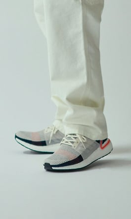 new arrival d2266 50669 A person with white pants wearing a pair of running shoes from adidas.