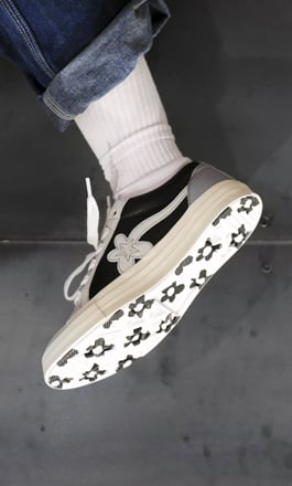 138215bd7621 A photo of a person with white socks wear a pair of converse shoes.