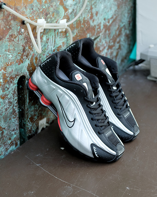 promo code d3299 e00c4 Nike sneakers, clothes and accessories. A pair of Nike Shox R4 sneakers in  black laying against a green old wall.
