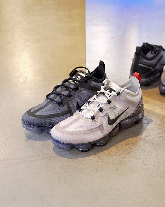 big sale b7f76 a8a4b A pair of Nike Vapormax sneakers in black and beige laying on a cement  floor.