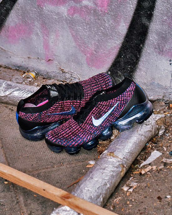 cheap for discount 3e7b9 354cf A pair of Nike Vapormax sneakers in purple laying against a spray painted  wall.